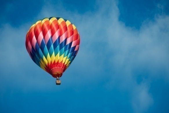Brightly colored hot air balloon with a sky blue background