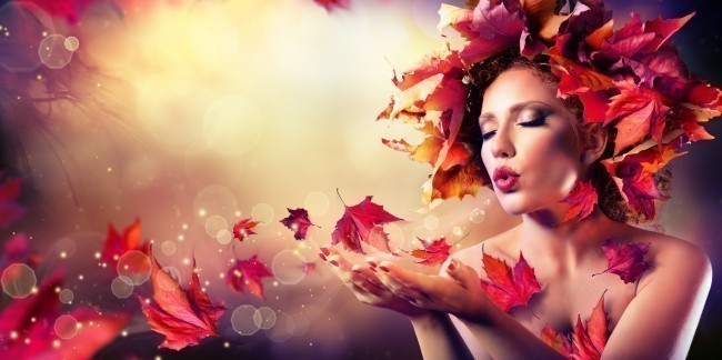 Autumn woman blowing red leaves