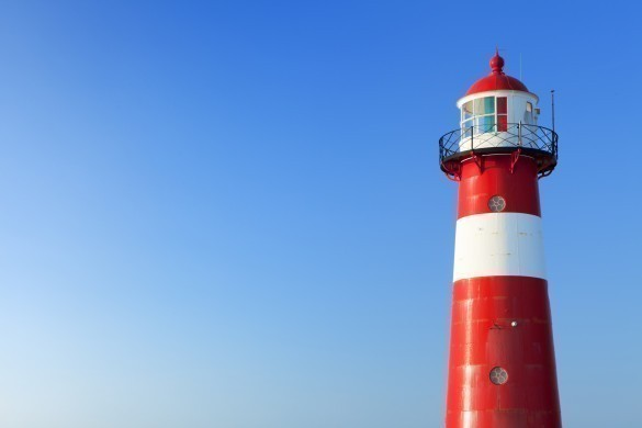 Red and white lighthouse and a clear blue sky