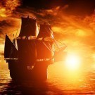 Ancient pirate ship sailing on the ocean at sunset