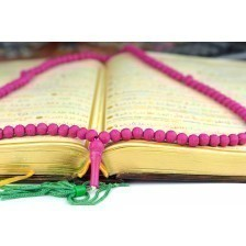Holy Koran with a rosary praying beads