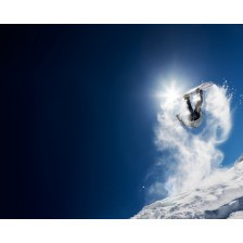 Snowboarder making high jump in clear blue sky